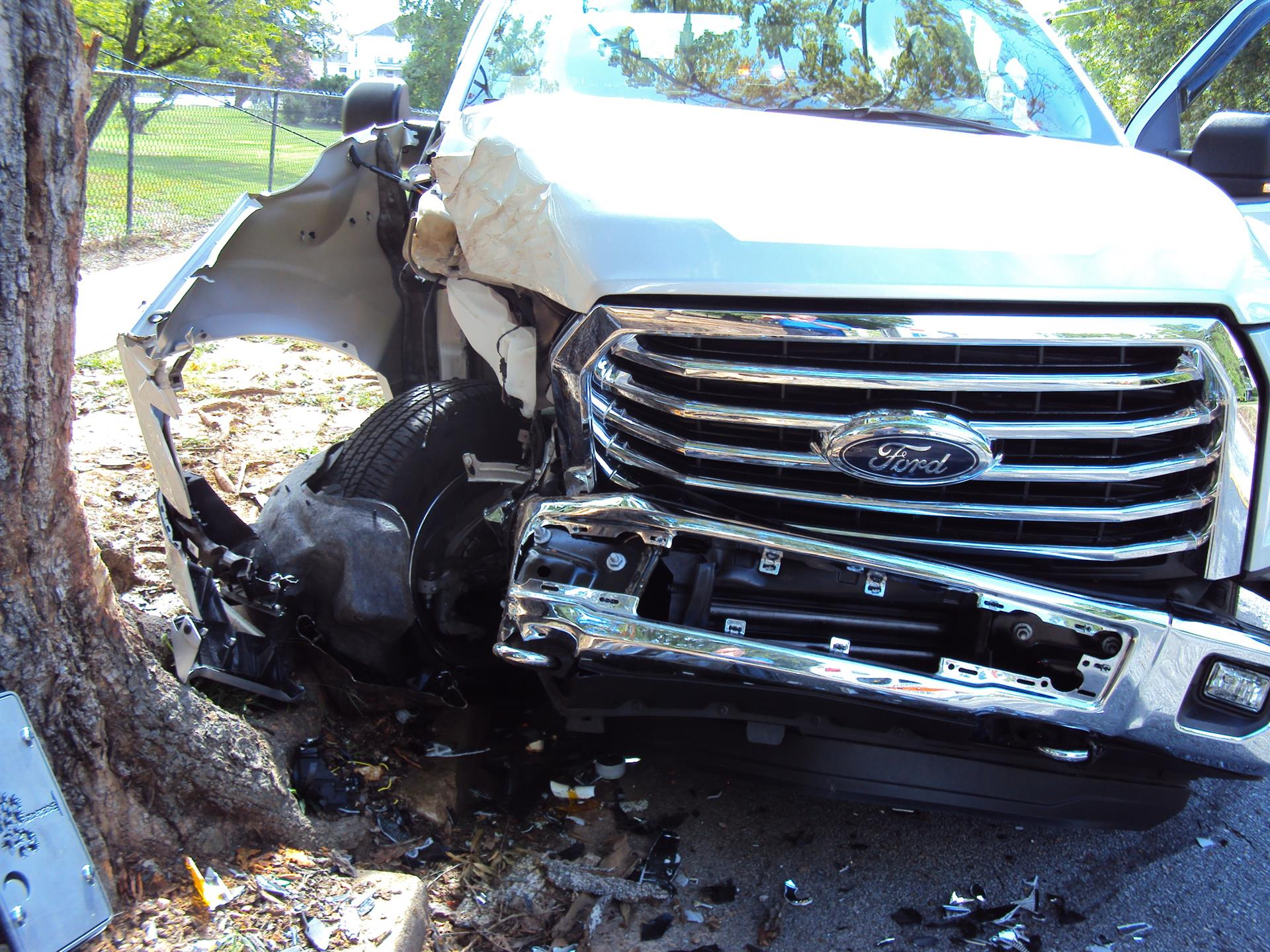 Truck crashed against tree with dislodged front tire