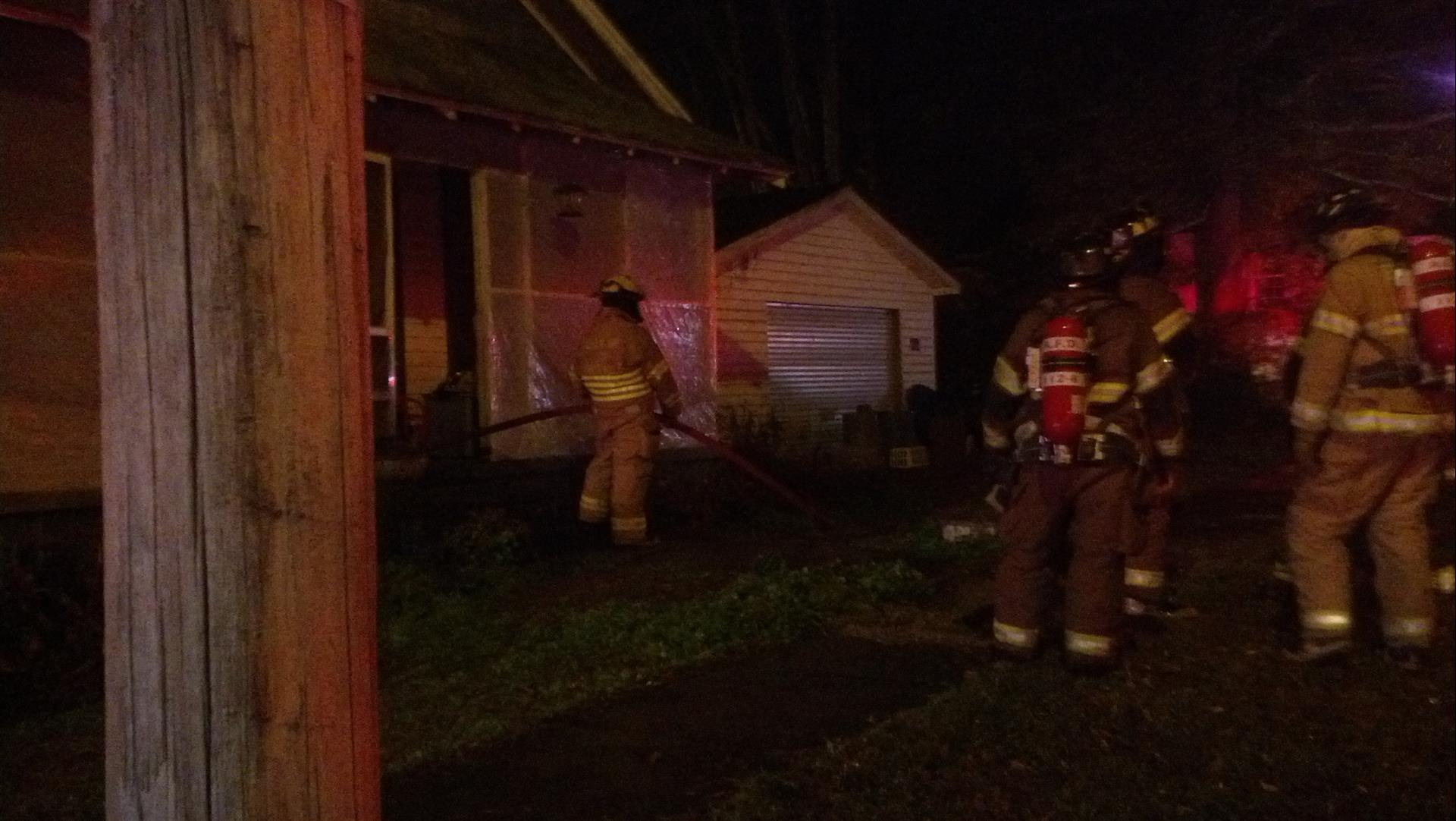 Firefighters use hose at night